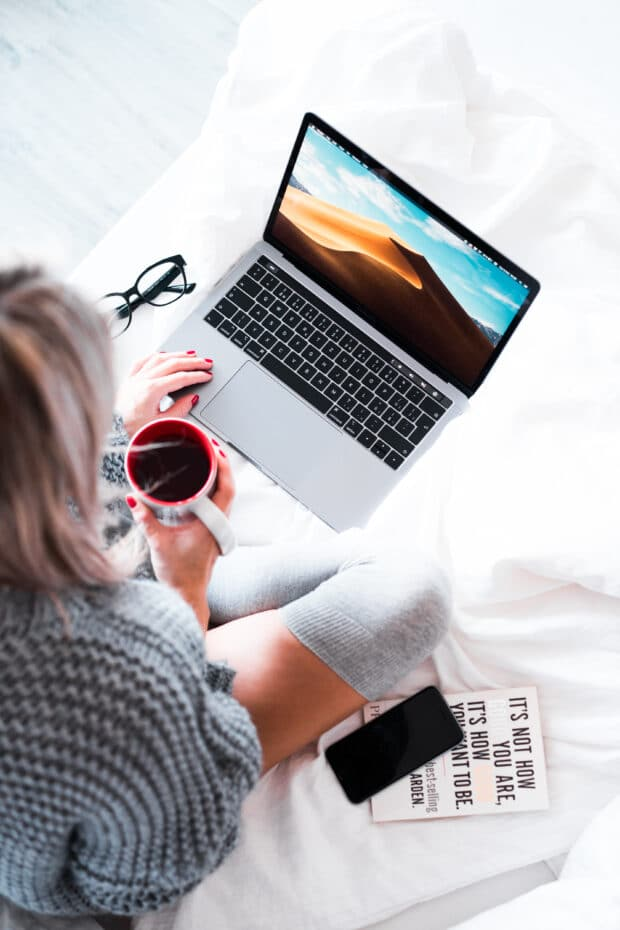 woman holding cup of coffee and working on laptop