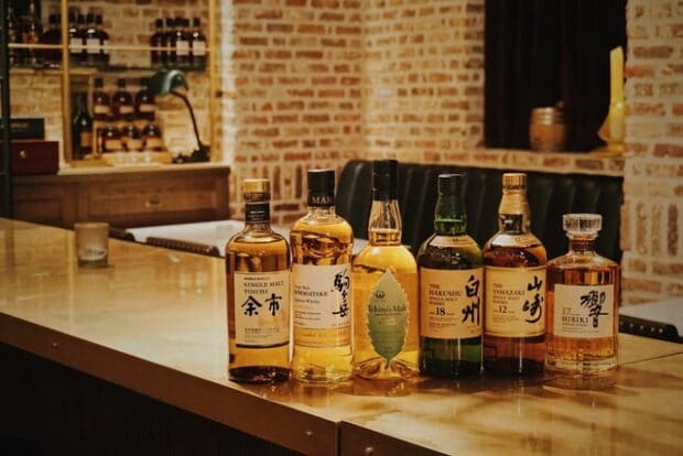 bottles of whiskey lined up in a bar
